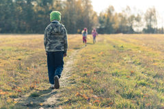 Sad boy walking behind laughing children royalty free stock photo