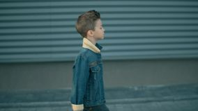 Alone little boy is walking down the street and thinking. Face of a little serious sad boy being. Sad boy is walking down the street and thinking. Face of a stock video