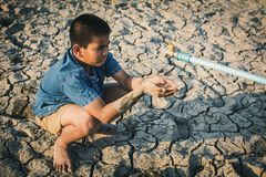 Sad boy want to drink some water on crack ground. Concept drought and shortage of water crisis royalty free stock photos