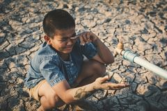 Sad boy want to drink some water on crack ground. Concept drought and shortage of water crisis royalty free stock photography