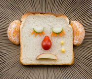 Sad bread face on ceramic plate. Funny sad face made with bread, fruit and vegetables Royalty Free Stock Photos