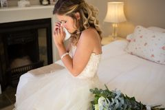 Sad bride crying while sitting on bed Stock Photo