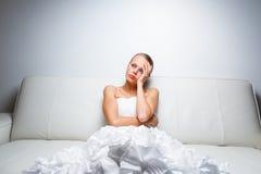 Sad bride crying sitting on a sofa