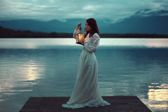 Sad bride on lake pier with lantern Royalty Free Stock Photos