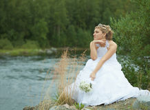 Sad bride sits on river bank Stock Image