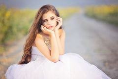 Sad bride. Bride wearing a white wedding gown on the country road Royalty Free Stock Photography