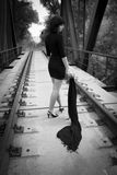 Sad brunette. Beautiful brunette with a shawl in her hand stands on a railway bridge Stock Images
