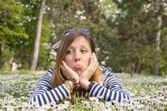 Sad brunette girl lying in the grass Stock Images
