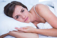 Sad brunette looking at camera in her bed Royalty Free Stock Image