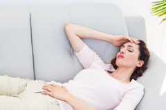 Sad brunette lying on the couch Royalty Free Stock Images