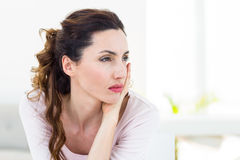 Sad brunette sitting on the couch Royalty Free Stock Image