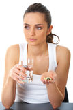 Sad brunette takes some pills. Stressed attractive young brunette take some pills, holds glass of water, isolated on white stock photography