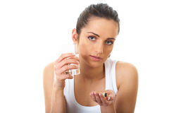 Sad brunette takes some pills,glass of water. Stressed attractive young brunette take some pills, holds glass of water, isolated on white royalty free stock image