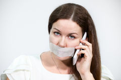 Sad brunette woman with cellphone and tape on her lips, grey background Royalty Free Stock Photography