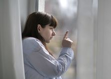 Sad young brunette woman looks out the window, finger on the glass stock images