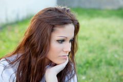 Sad brunette woman in park thinking Royalty Free Stock Photos
