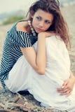 Sad brunette woman sitting on beach. Beautiful sad brunette woman sitting on beach Stock Photo