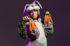 Sad bunny girl with big ears. And holding a bunch of carrots. Dark colored background royalty free stock images