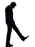 Sad business man looking down silhouette. One caucasian sad business man looking down in silhouette studio on white background royalty free stock photo