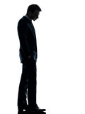 Sad business man  looking down silhouette. One caucasian sad business man  looking down  in silhouette studio isolated on white background Royalty Free Stock Photo