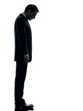 Sad business man  looking down silhouette. One caucasian sad business man  looking down  in silhouette studio  on white background Royalty Free Stock Image