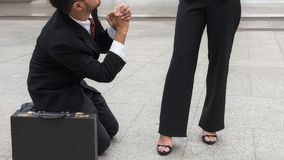 Businessman ask female boss for sympathy. Sad Business men  kneel and raise hands to ask for sympathy after he not get promote or be punished outside office Stock Photo