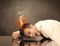 Sad business person`s head catching fire. A frustrated businessman resting his head on a keyboard and shouting with his hair on smoke, catching fire Stock Images