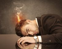 Sad business person`s head catching fire. A frustrated businessman resting his head on a keyboard and shouting with his hair on smoke, catching fire Royalty Free Stock Photography