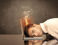 Sad business person's head catching fire. A frustrated businessman resting his head on a keyboard and shouting with his hair on smoke, catching fire Royalty Free Stock Image