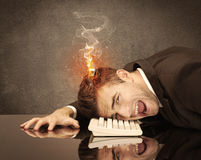 Sad business person's head catching fire. A frustrated businessman resting his head on a keyboard and shouting with his hair on smoke, catching fire Stock Photo