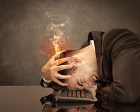 Sad business person's head catching fire. A frustrated businessman resting his head on a keyboard and shouting with his hair on smoke, catching fire Royalty Free Stock Photography