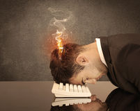 Sad business person's head catching fire. A frustrated businessman resting his head on a keyboard and shouting with his hair on smoke, catching fire Stock Images