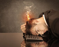 Sad business person's head catching fire. A frustrated businessman resting his head on a keyboard and shouting with his hair on smoke, catching fire Royalty Free Stock Photo