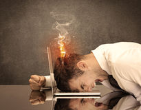 Sad business person`s head catching fire. A frustrated businessman resting his head on a keyboard and shouting with his hair on smoke, catching fire Royalty Free Stock Images