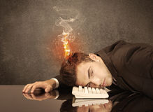 Sad business person`s head catching fire. A frustrated businessman resting his head on a keyboard and shouting with his hair on smoke, catching fire Stock Photos
