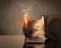 Sad business person`s head catching fire. A frustrated businessman resting his head on a keyboard and shouting with his hair on smoke, catching fire Stock Photo