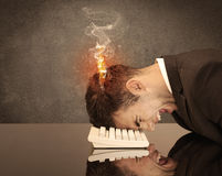 Sad business person`s head catching fire. A frustrated businessman resting his head on a keyboard and shouting with his hair on smoke, catching fire Stock Image