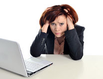 Sad business red haired woman in stress at work with computer. Sad business woman in stress at work with computer pulling her red hair isolated on white Stock Photography