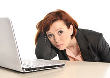 Sad business red haired woman in stress at work with computer. Isolated on white background Royalty Free Stock Photos