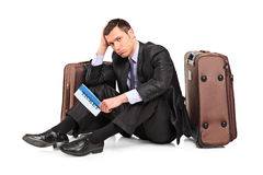Sad business traveler seated next to a suitcase. A sad business traveler seated next to a suitcase with a ticket in his hand isolated on white background Royalty Free Stock Photography