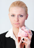 Sad business woman with broken piggybank. Sad businesswoman with broken piggybank on her hand Stock Images