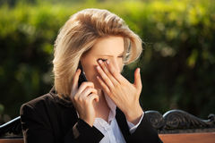 Sad businesswoman calling on the cell phone. Sad business woman calling on the cell phone in a city park Stock Image