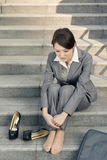 Sad business woman feel helpless. And sit on stairs in modern city Stock Photography