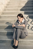 Sad business woman feel helpless. And sit on stairs in modern city Royalty Free Stock Photography