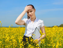 Sad business woman in flower field outdoor with clipboard touch head. Young girl in yellow rapeseed field. Beautiful spring landsc Stock Photo