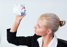 Sad Business woman looking into Piggy Bank Royalty Free Stock Image