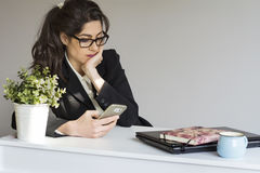 Sad  business woman in office with phone in the hands Royalty Free Stock Image