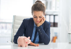 Sad business woman with piggy bank looking on coin royalty free stock image
