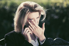 Sad business woman talking on cell phone in a city park Royalty Free Stock Image