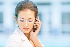 Sad business woman talks by phone. Young beautiful sad business woman in glasses talks by mobile phone and looks downwards against magnificent office Stock Image